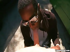 Ebony dude in glasses throats white cock outdoor